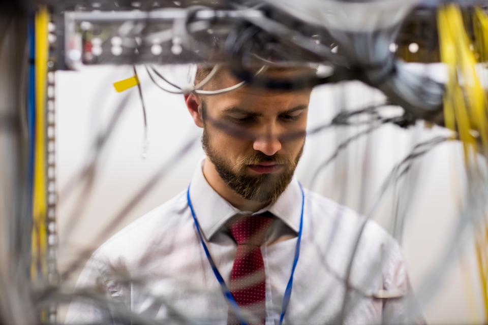 """""""Technician checking cables in a rack mounted server"""" stock image"""