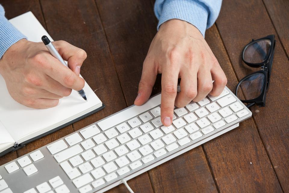 """Man typing on keyboard and writing in diary"" stock image"