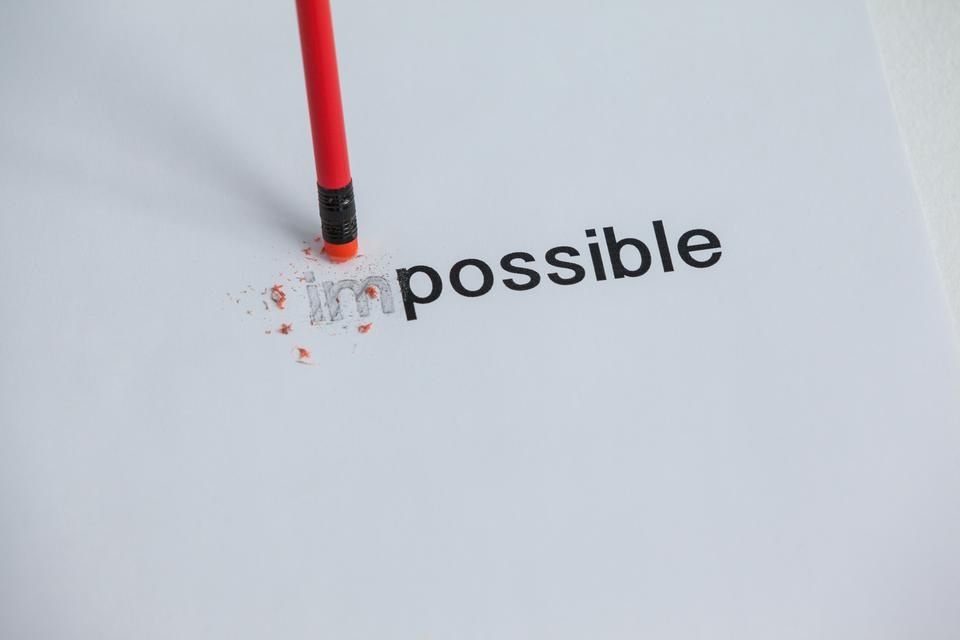 """""""Changing the word impossible to possible with a pencil eraser"""" stock image"""