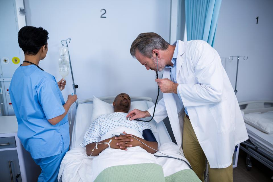 """Doctor checking patient heartbeat with stethoscope in ward"" stock image"