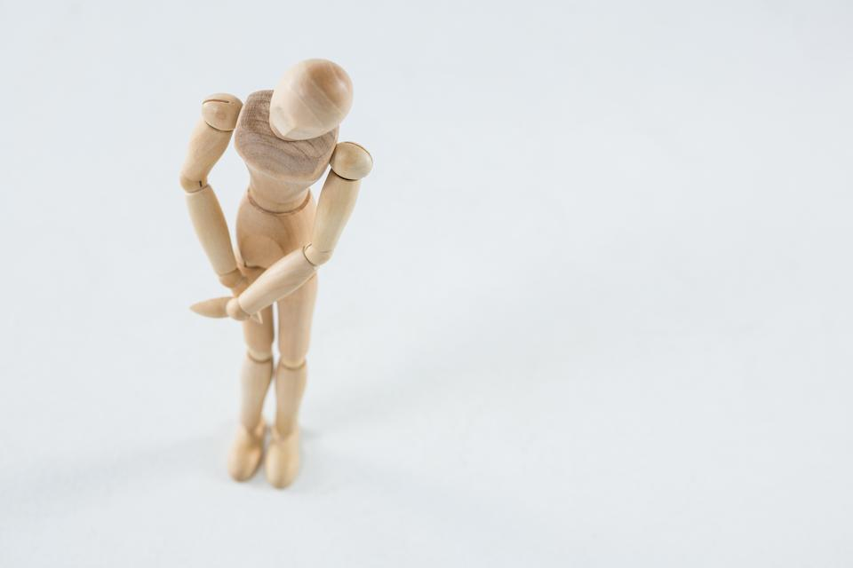 """Wooden figurine with leg injured"" stock image"