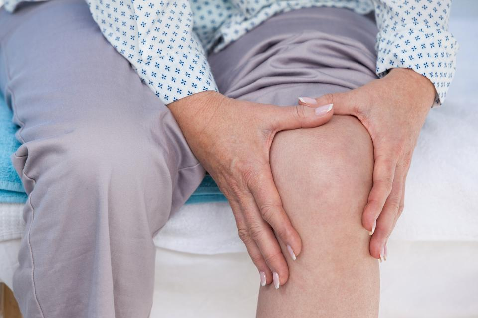 """Patient touching her injured knee"" stock image"