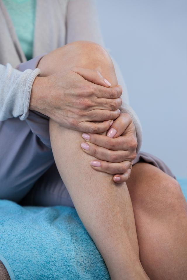 """Patient holding her injured knee"" stock image"