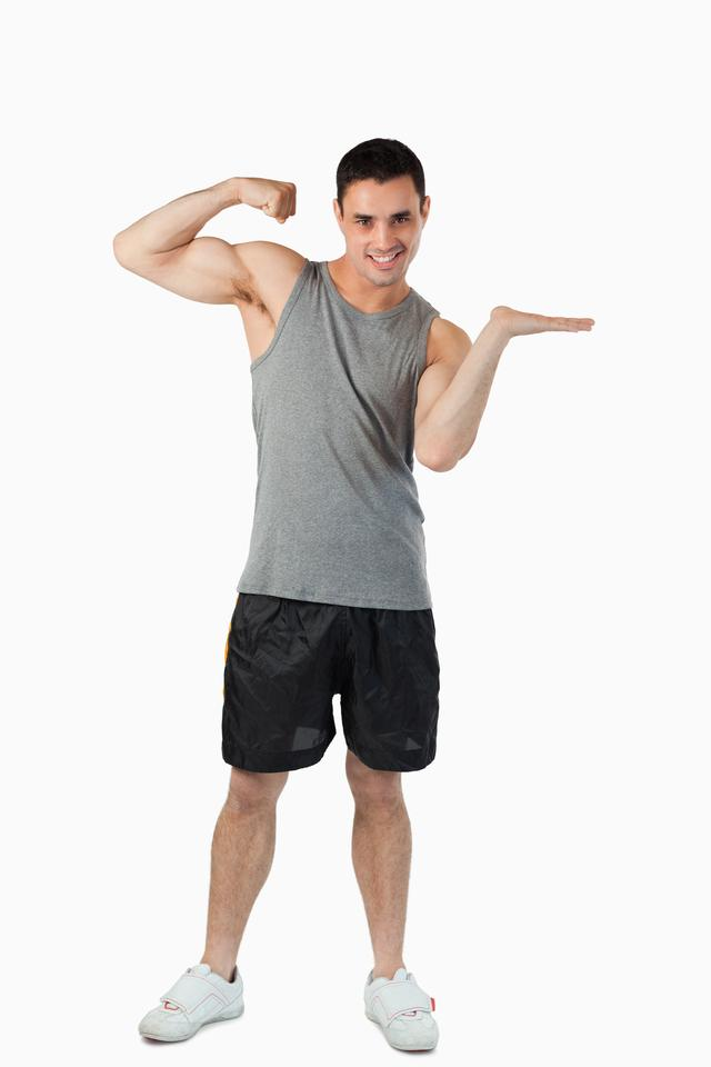 """""""Young man showing his biceps while presenting"""" stock image"""