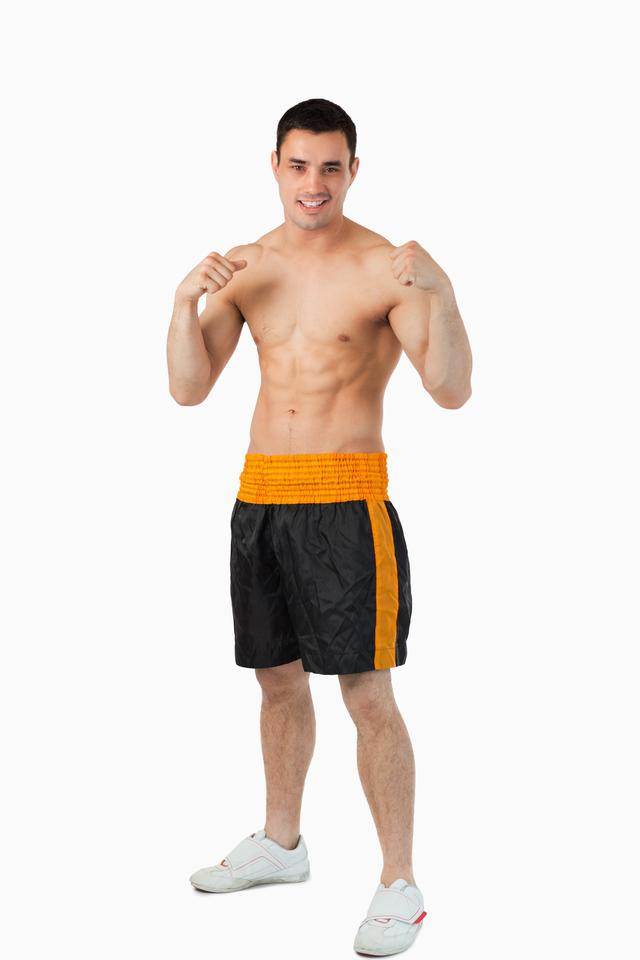 """""""Smiling young boxer with bare fists up"""" stock image"""