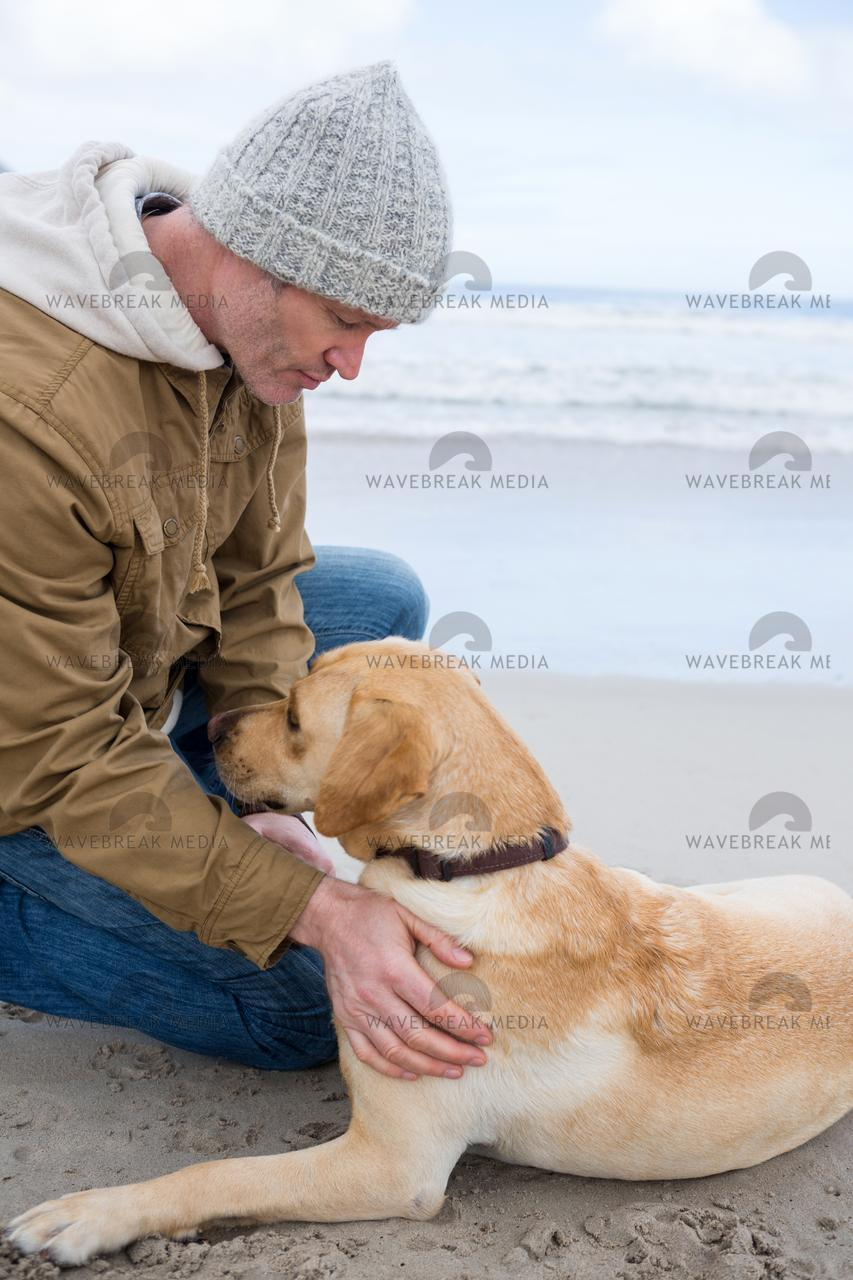 """Man pampering dog while sitting"" stock image"