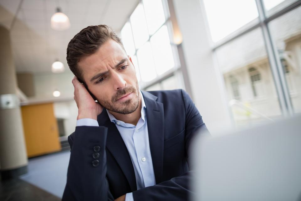 """""""Worried businessman sitting at desk with laptop"""" stock image"""