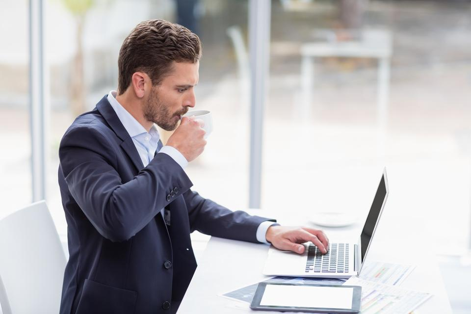 """""""Businessman using laptop at desk and drinking coffee"""" stock image"""