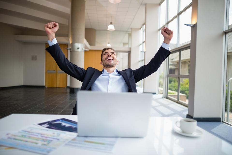 """""""Businessman sitting at desk with arms outstretched"""" stock image"""