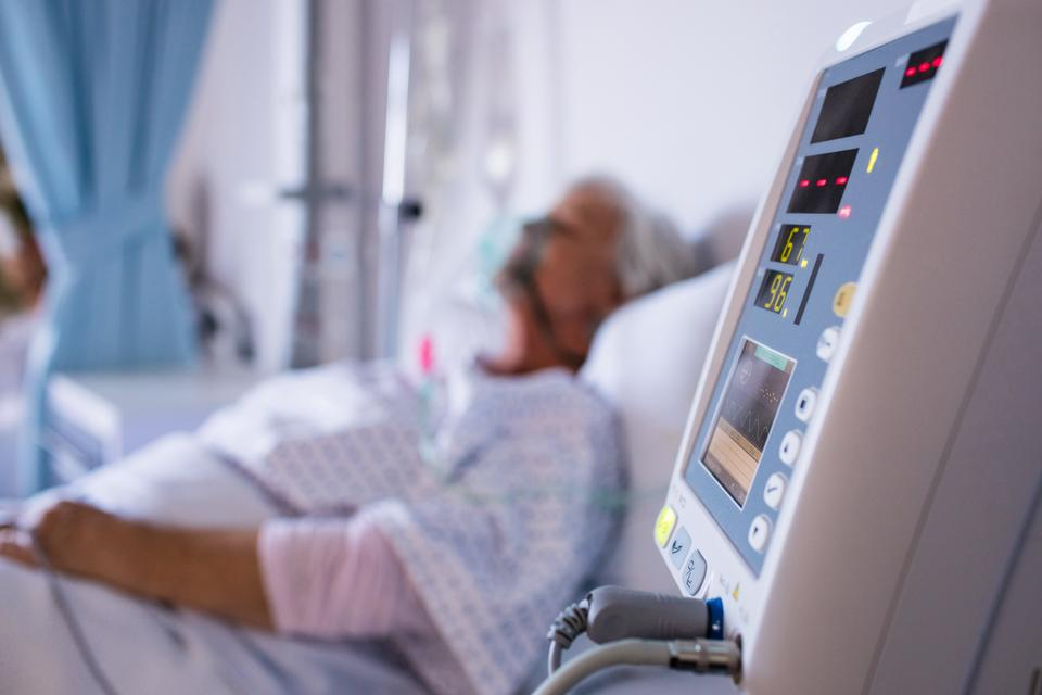 """Close-up of vital signs monitor with senior patient in the background"" stock image"