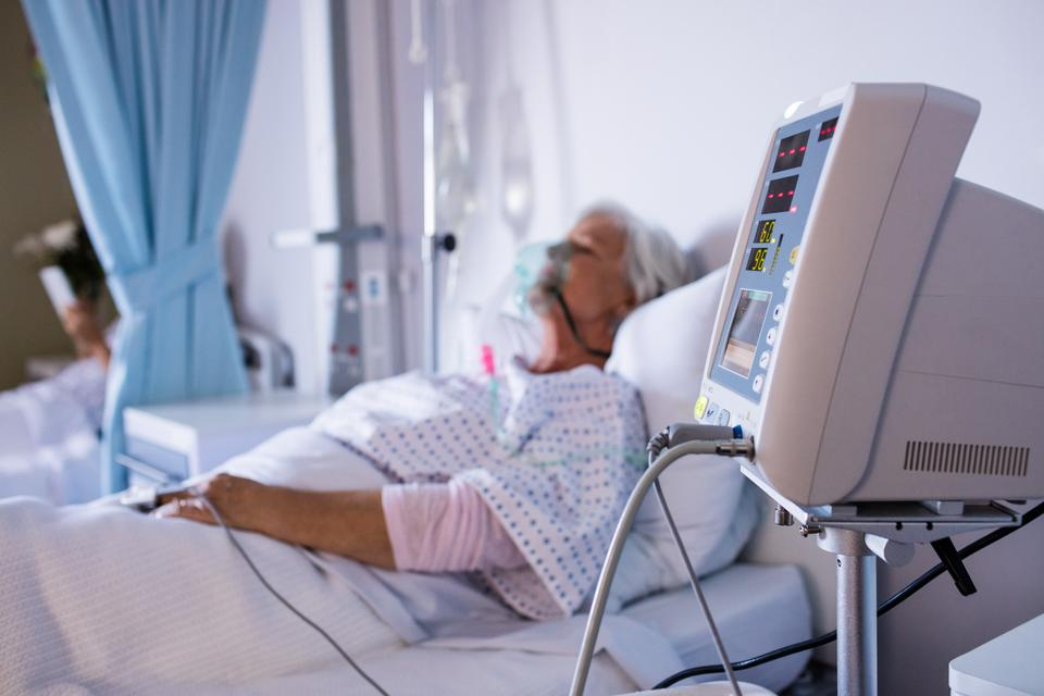 """Vital signs monitor with senior patient relaxing in the background"" stock image"