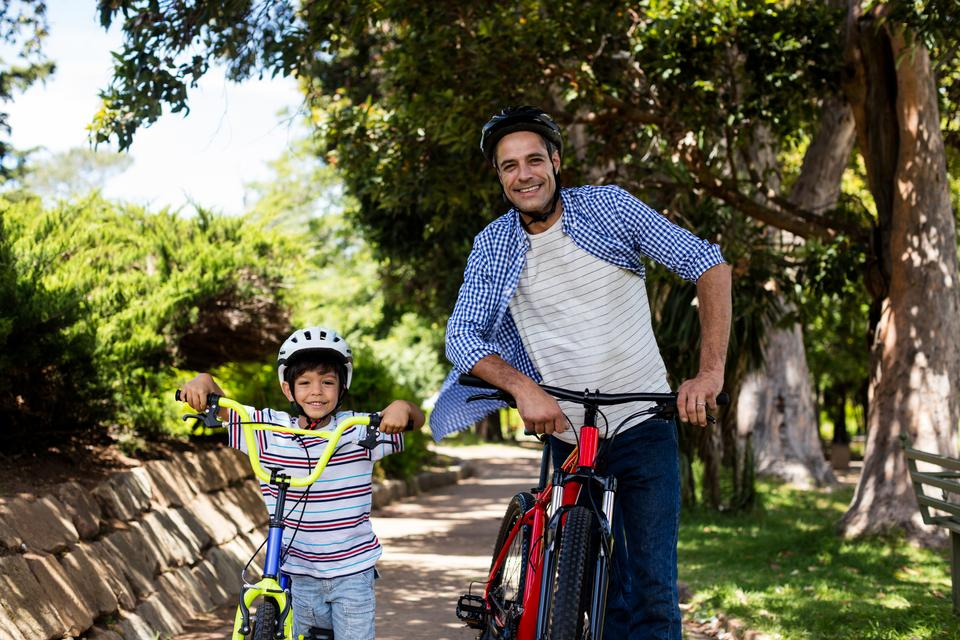 """Portrait of father and son standing with bicycle in park"" stock image"