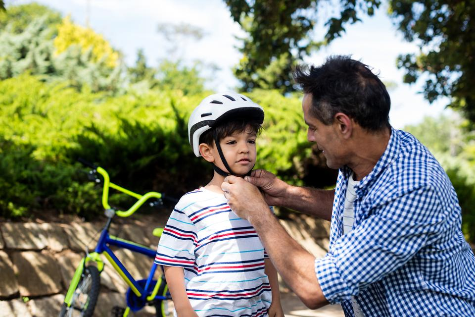 """Father assisting son in wearing bicycle helmet in park"" stock image"