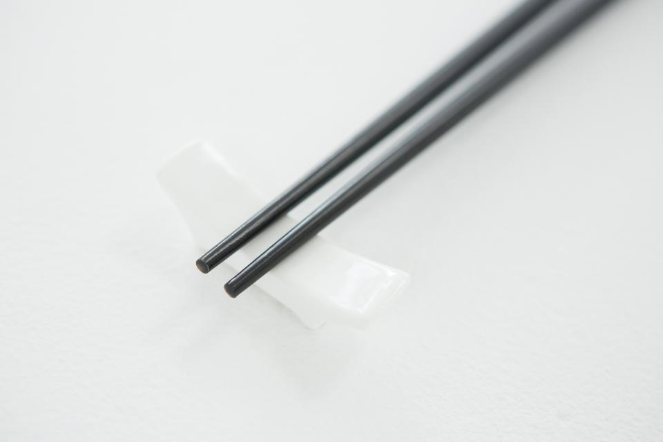 """Black chopsticks on a chopstick rest"" stock image"