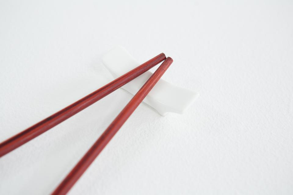 """Red chopsticks on a chopstick rest"" stock image"