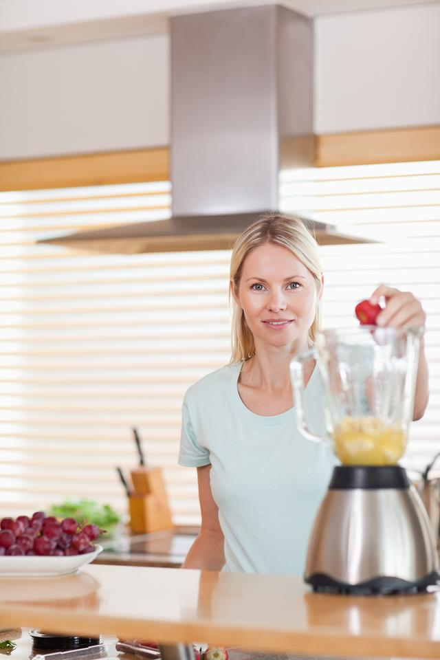 """Woman putting strawberry into the blender"" stock image"