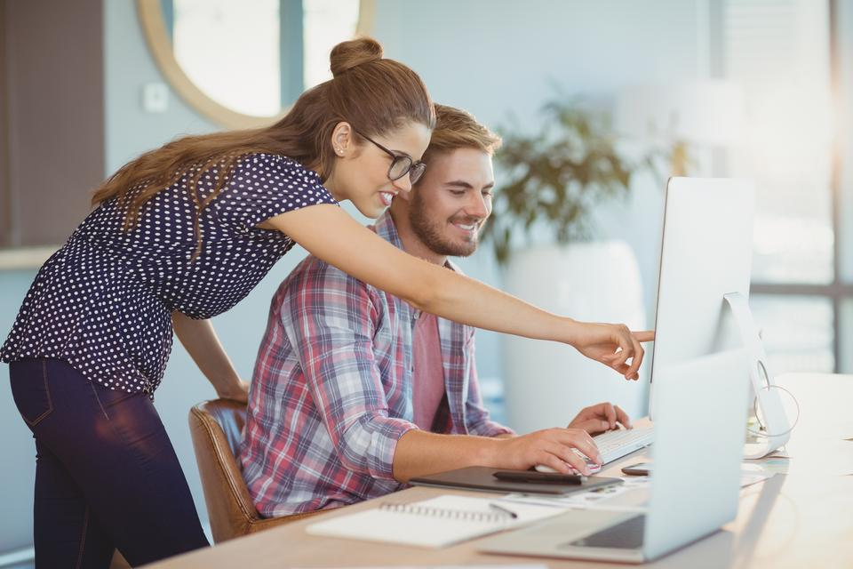 """""""Graphic designers discussing over personal computer"""" stock image"""