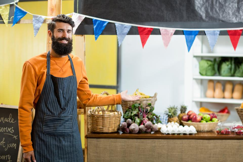 """""""Vendor pointing towards counter in grocery store"""" stock image"""