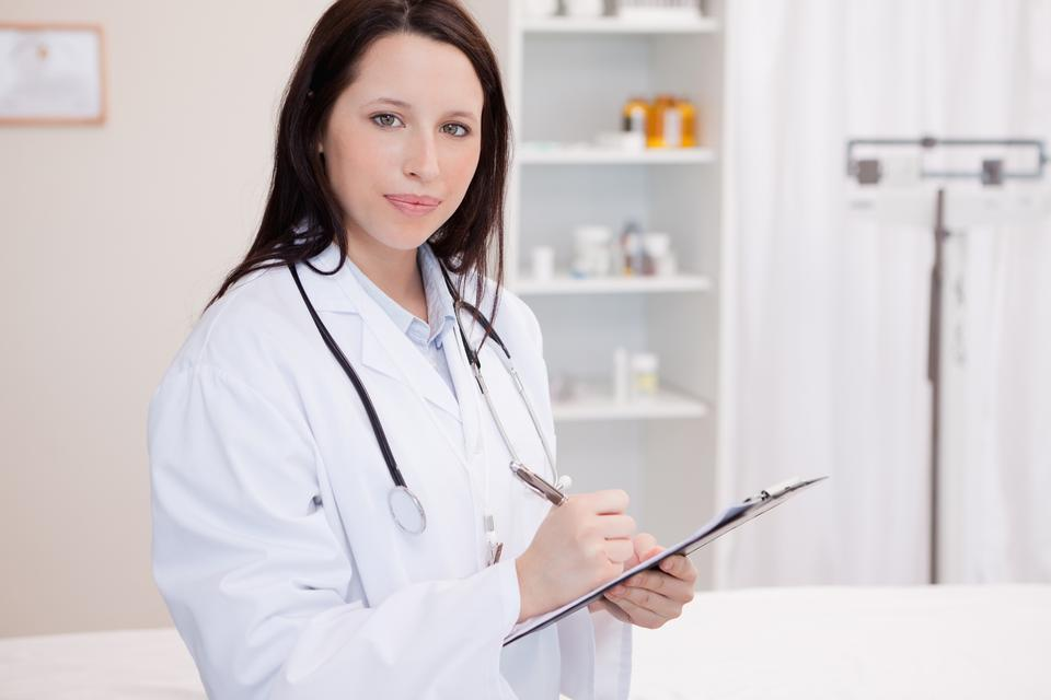 """Female physician taking notes"" stock image"