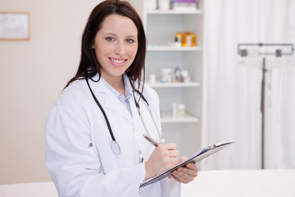 """Smiling female physician taking notes"" stock image"