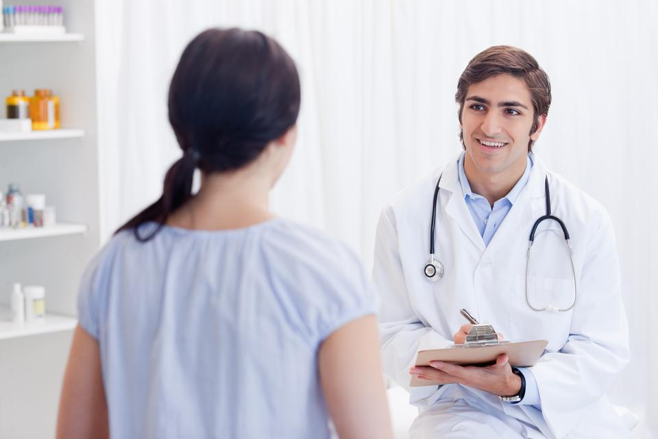 """Smiling physician talking with patient"" stock image"