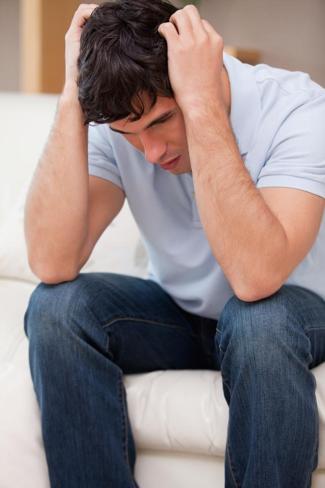 """""""Frustrated man sitting on the couch"""" stock image"""