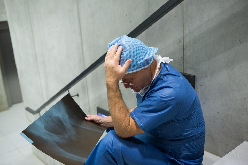 """""""Tensed male surgeon examine x-ray on staircase"""" stock image"""