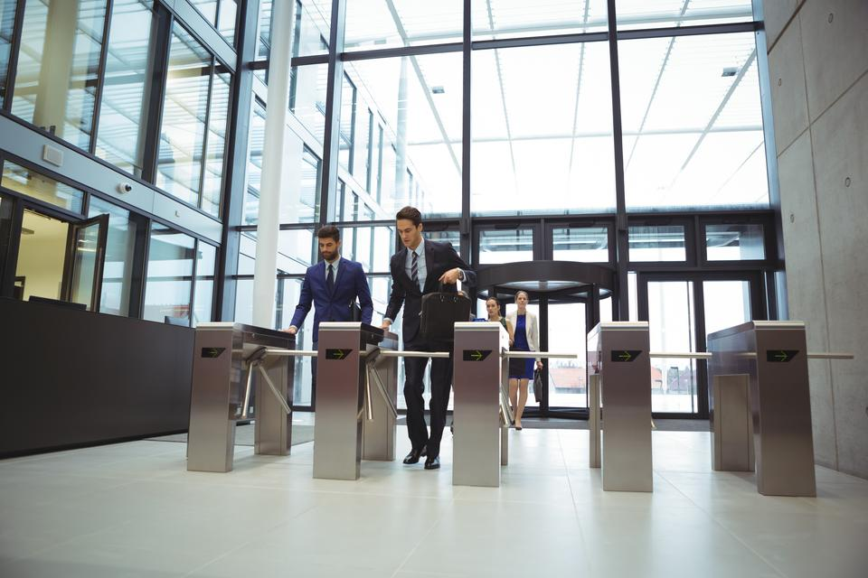 """""""Businesspeople scanning their cards at turnstile gate"""" stock image"""