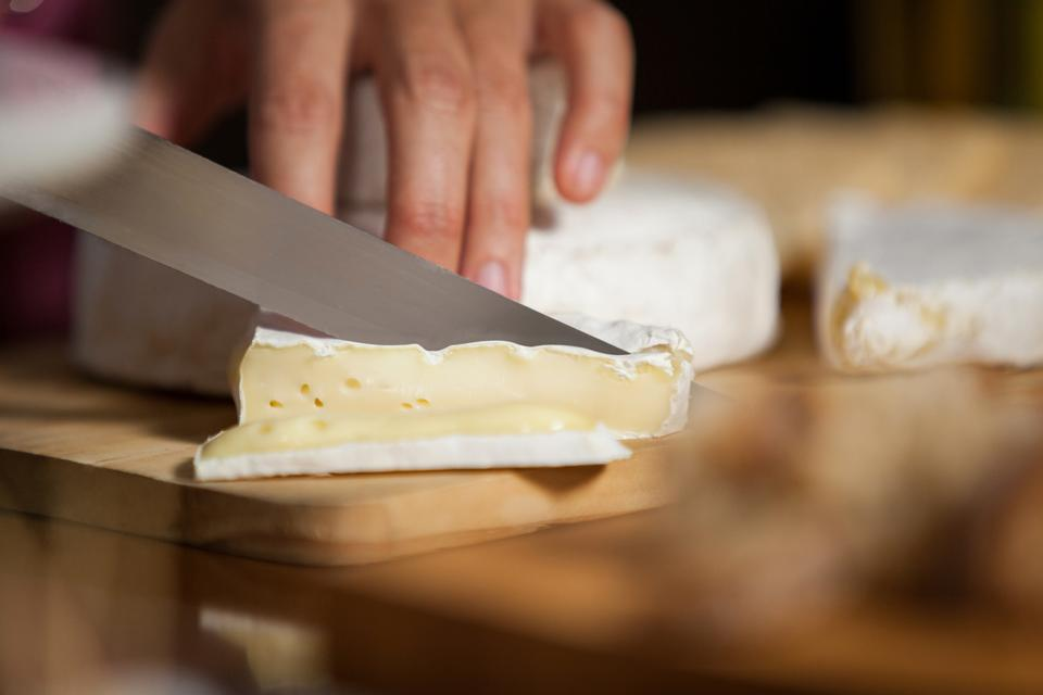 """Female staff cutting cheese at counter in market"" stock image"