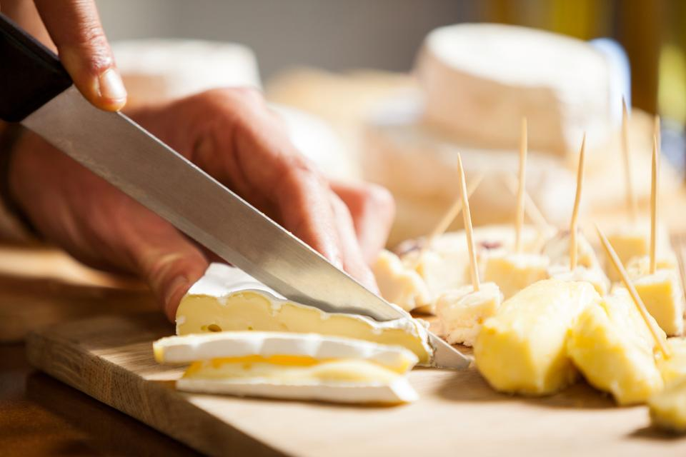 """Staff cutting cheese at counter in market"" stock image"