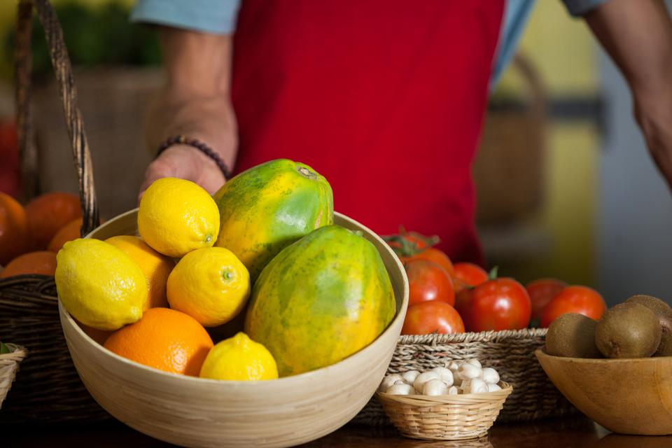 """Staff holding a bowl of fruits at counter in market"" stock image"