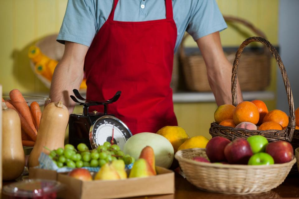 """Staff standing at counter in market"" stock image"