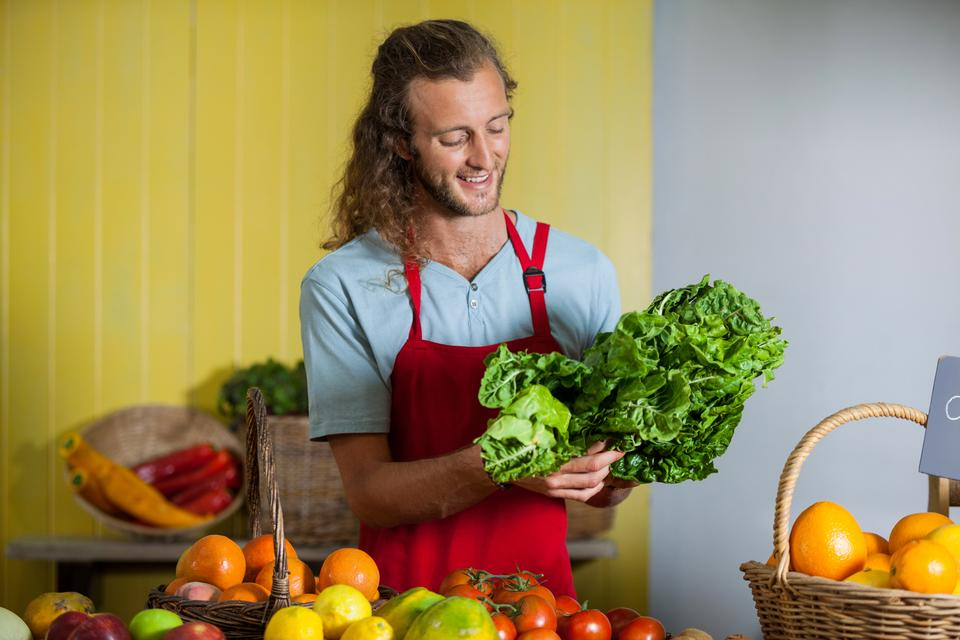 """Smiling staff looking at leafy vegetables at counter"" stock image"