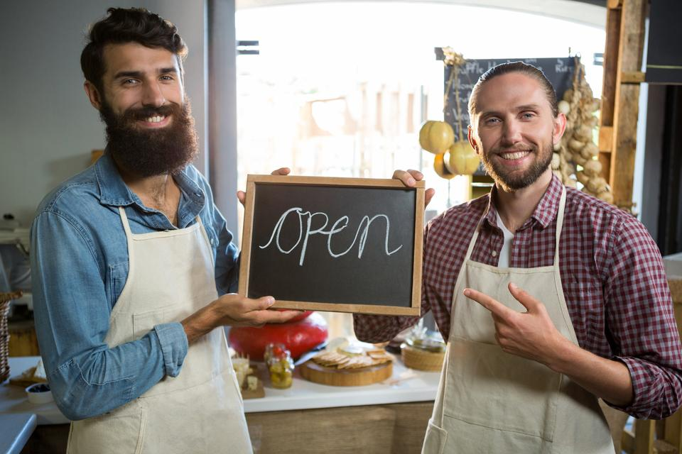 """Smiling male staffs holding a open sign"" stock image"