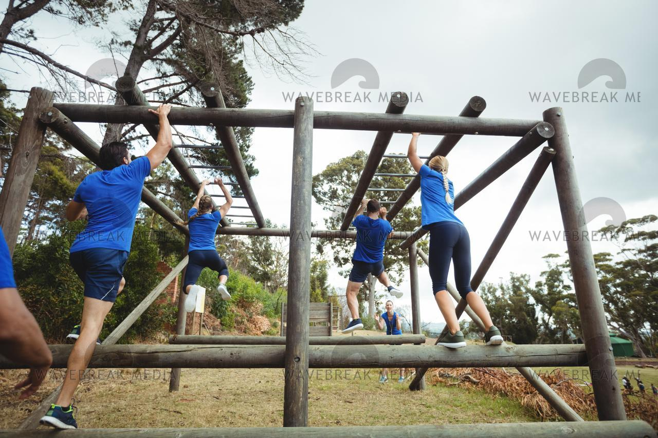 Fit people climbing monkey bars in bootcamp - License
