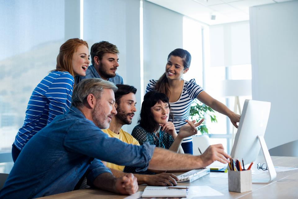 """""""Creative business team discussing while working together on desktop pc in office"""" stock image"""