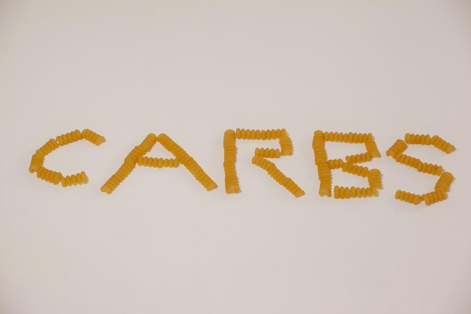 """""""Conchiglie pasta arrange in shape of carbs text"""" stock image"""