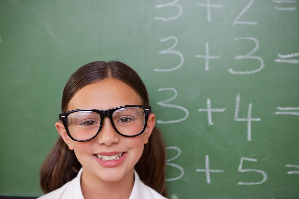 """Smiling smart schoolgirl posing"" stock image"