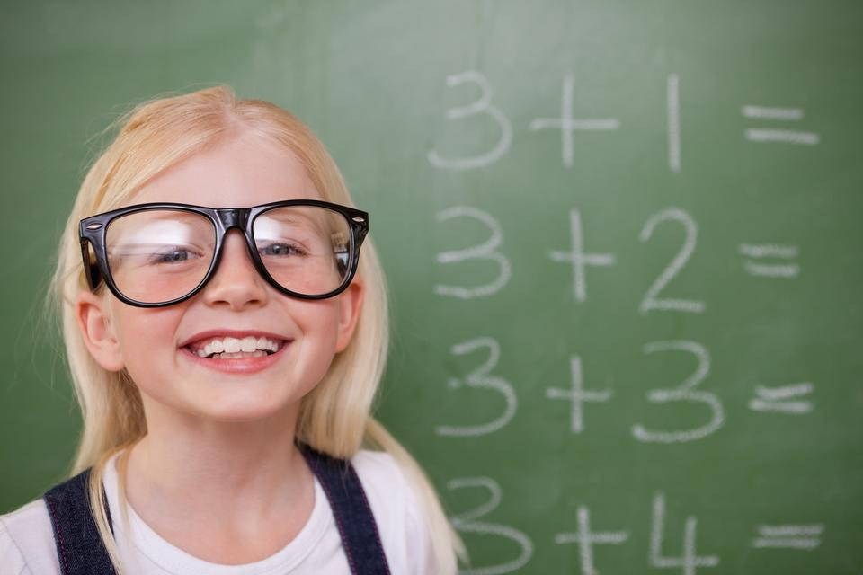 """Smart schoolgirl posing in front of a blackboard"" stock image"
