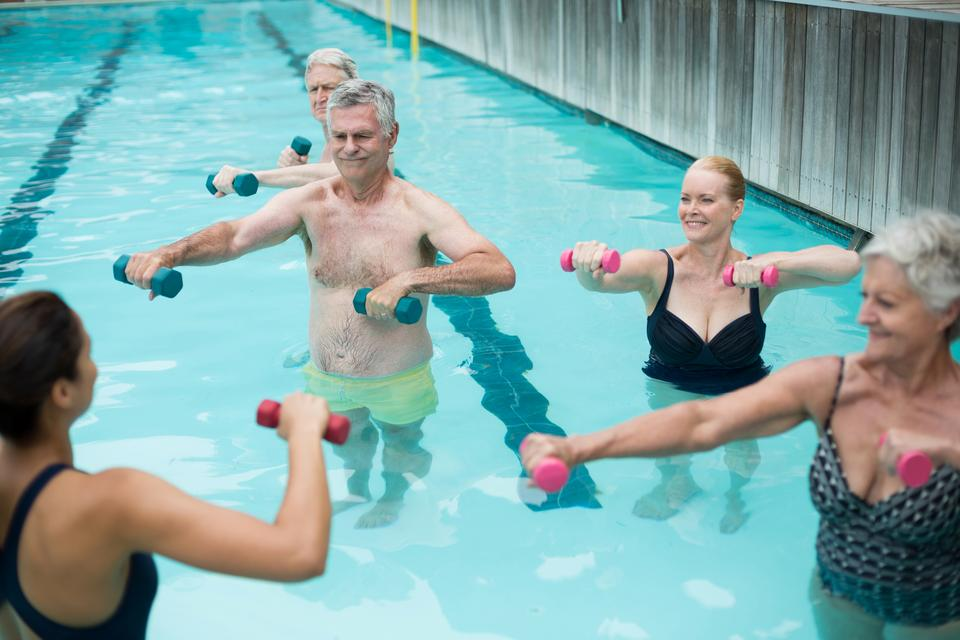 """""""Senior swimmers and instructor lifting dumbbells in swimming pool"""" stock image"""