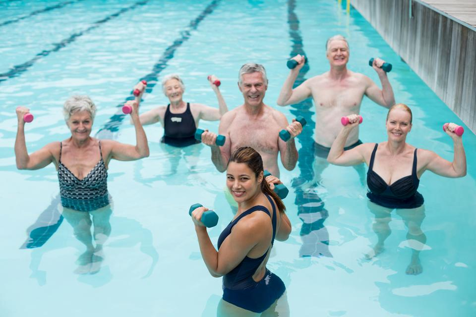 """""""Senior swimmers and trainer lifting dumbbells in swimming pool"""" stock image"""