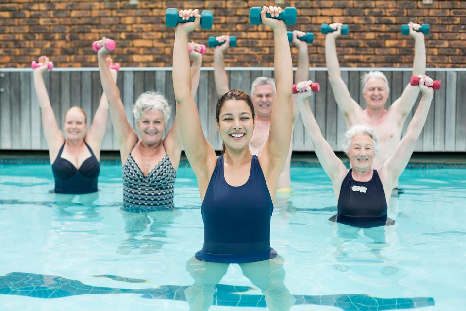 """""""Senior swimmers lifting dumbbells in swimming pool"""" stock image"""