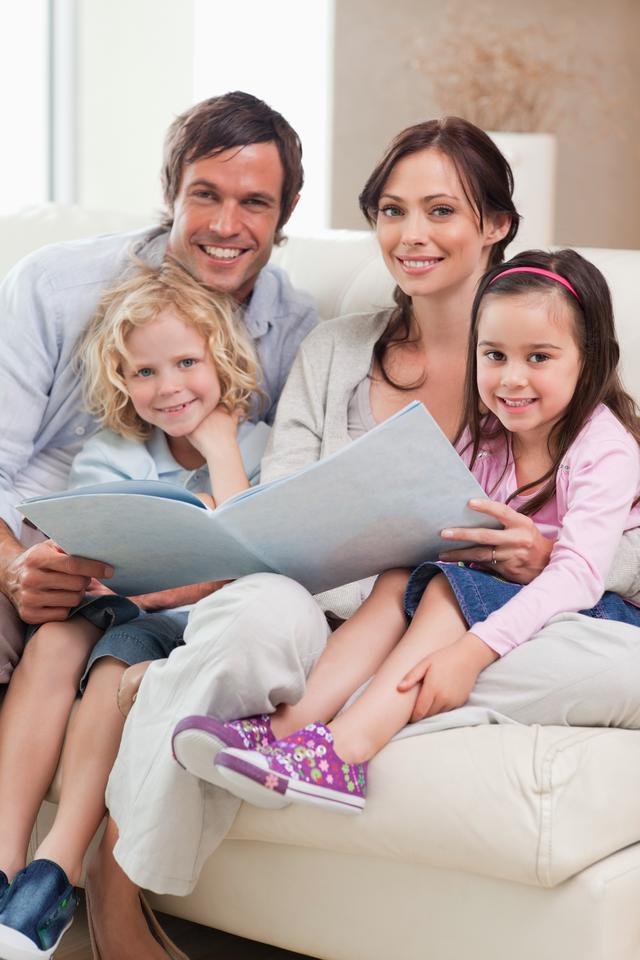 """""""Portrait of a family looking at a photo album"""" stock image"""