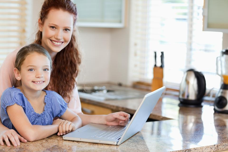 """""""Mother and daughter surfing the internet in the kitchen"""" stock image"""