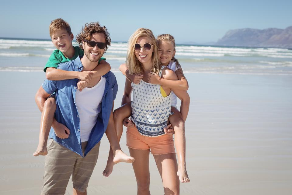 """""""Portrait of smiling parents piggybacking their children at beach"""" stock image"""