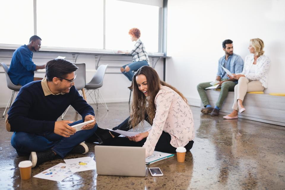 """""""Happy business colleagues working on floor at office"""" stock image"""