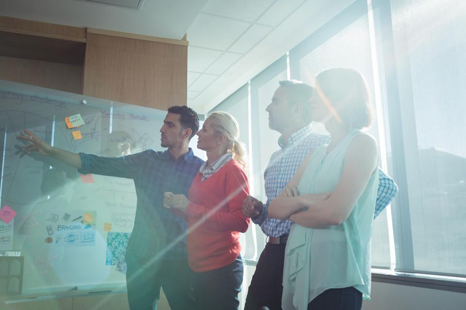 """""""Business colleagues discussing by whiteboard at office"""" stock image"""