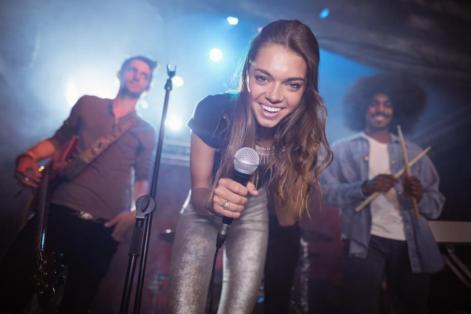 """Cheerful young singer with musicians performing at nightclub"" stock image"