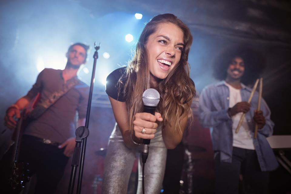 """Cheerful young woman with musicians performing at nightclub"" stock image"