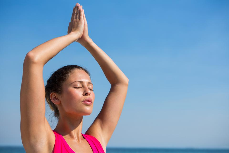 """""""Young woman against clear sky exercising at beach"""" stock image"""